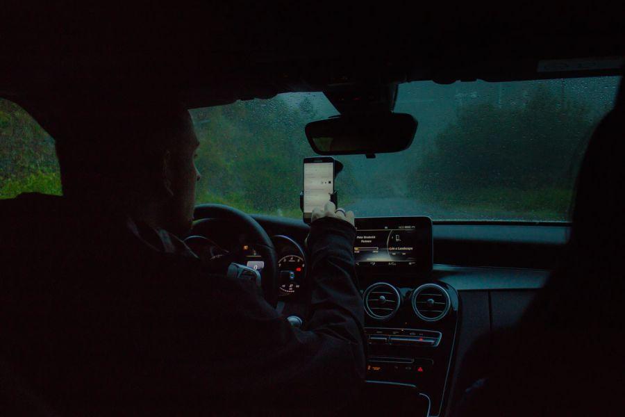 autó sofőrje telefonját nézi - Fotó: unsplash