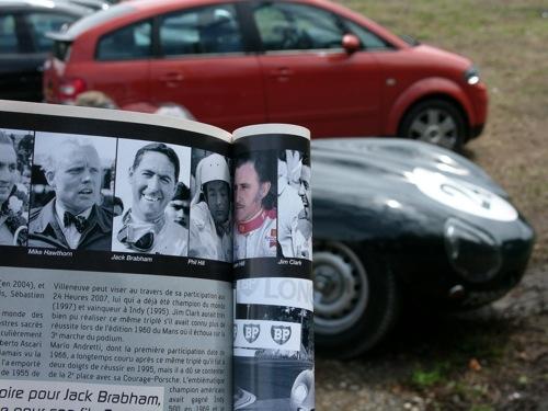 Mike Hawthorn a verseny programfüzetében, egy Jaguar D-Type előtt
