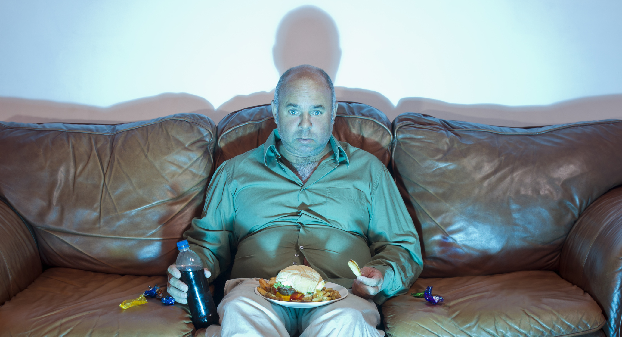 a-mature-overweight-man-sitting-on-an-old-couch-watching-tv-with-an-unhealthy-meal-of-hamburger-french-fries-and-soda-pop-2.jpg
