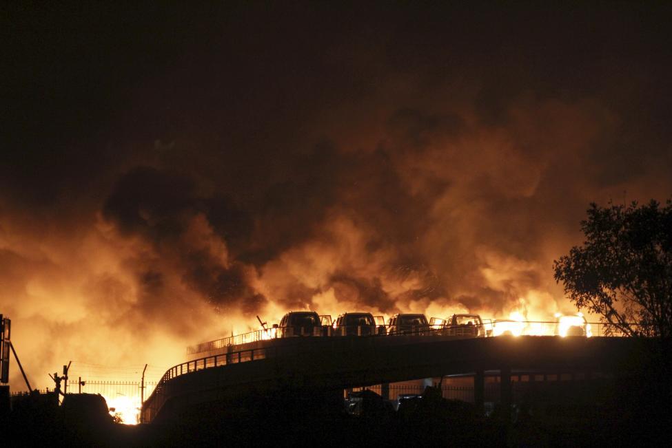 Gépkocsik lángolnak a Tiencsinben, Kínában lévő vegyiüzem raktár robbanása után. Az esetnek eddigi információk szerint legalább 50 halálos áldozata és közel 500 sebesültje van. (f.: Reuters)