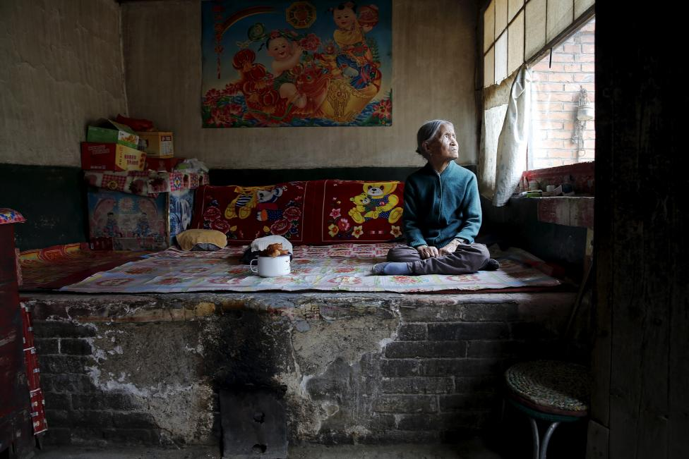 Kínai korábbi 'komfort hölgy' ül tradicionális téglából készített ágyán. A 'komfort hölgy' kifejezés azon fiatal lányokra volt használatos, akiket a japán hadsereg kényszerített prostitúcióra a második világháború alatt. Az idős hölgy az utolsó túlélője annak a 16 ilyen múlttal rendelkező nőnek, akik 1995-ben beperelték a japán államot. (f.: Reuters)