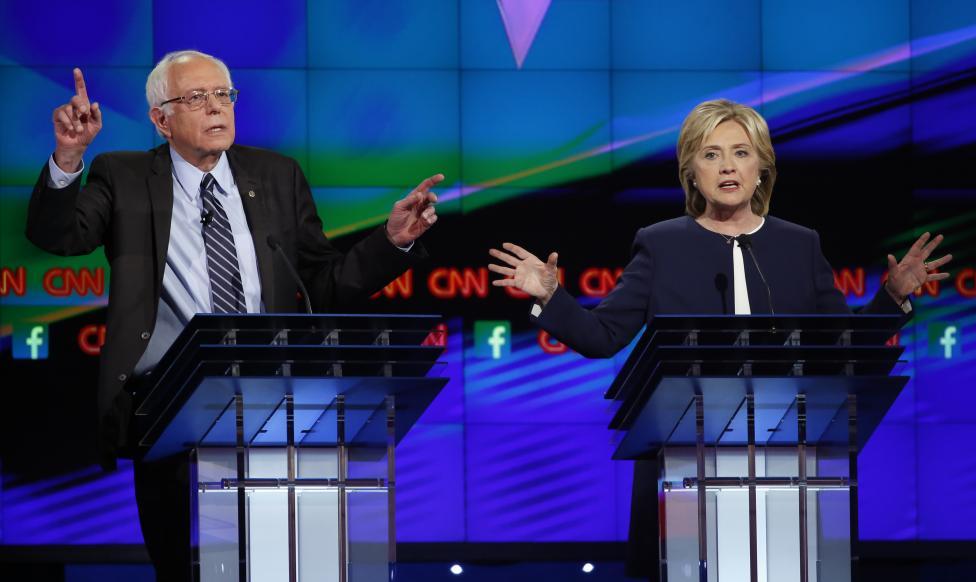 Bernie Sanders és Hillary Clinton gesztikulál a vita egyik hevesebb momentumai között. Clinton e-mail botránya továbbra is hangsúlyt kapott a vita során,amivel kapcsolatban megjegyezte: hiba volt a saját szerveréről kommunikálni, de hangsúlyozta, energiáit inkább a szavazók számára fontos kérdésekre kívánja irányítani.(f.: Reuters)