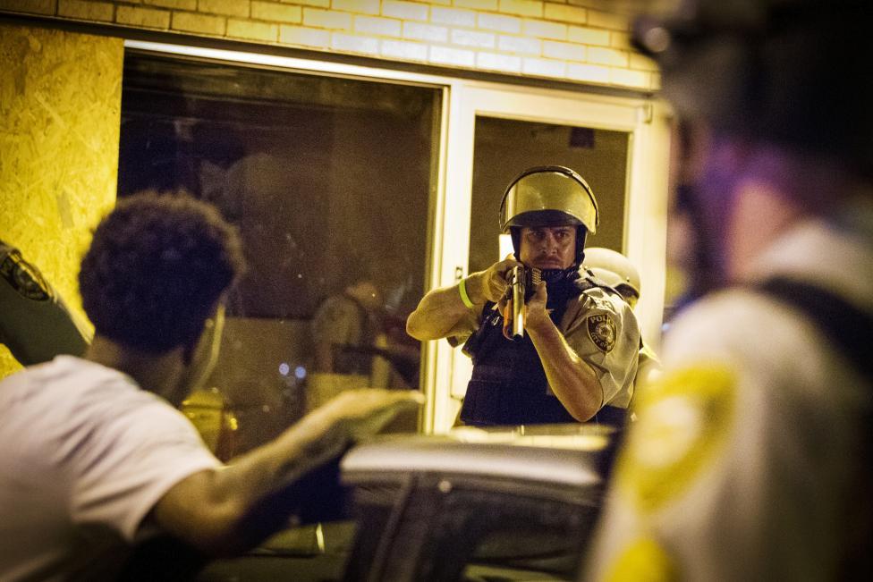 St. Louis megyei rendőr fog fegyvert és tartóztat le tüntetőket Fergusonban. Az Egyesült Államokban most tartották az egy évvel ezelőtti fergusoni esetre (amikor egy fehér rendőr minden valós indok nélkül lőtt le egy fegyvertelen fekete fiatalt) való megemlékezést. Az utcai demonstrációból zavargások alakultak ki, és rendkívüli állapotot hirdettek a városban. (f.: Reuters)