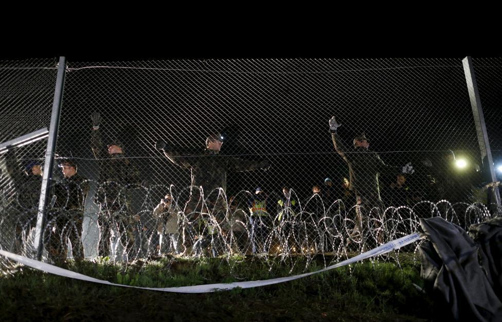 Ez azonban október 17-re (szombatra) virradóan megváltozni látszik, mivel a magyar kormány döntött az itteni határzár felállításáról is. A képen magyar honvédek építik a kerítést Botovo környékén. (f.: Reuters)