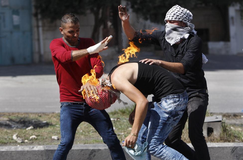 Palesztin tüntetők próbálják eloltani a lángokat egyik társukon, miután az sikertelenül próbált molotov koktélt dobni az izraeli katonákra. Kelet-Jeruzsálemben továbbra is feszült a biztonsági helyzet, több merénylet is történt az elmúlt napban. (f.: Reuters)