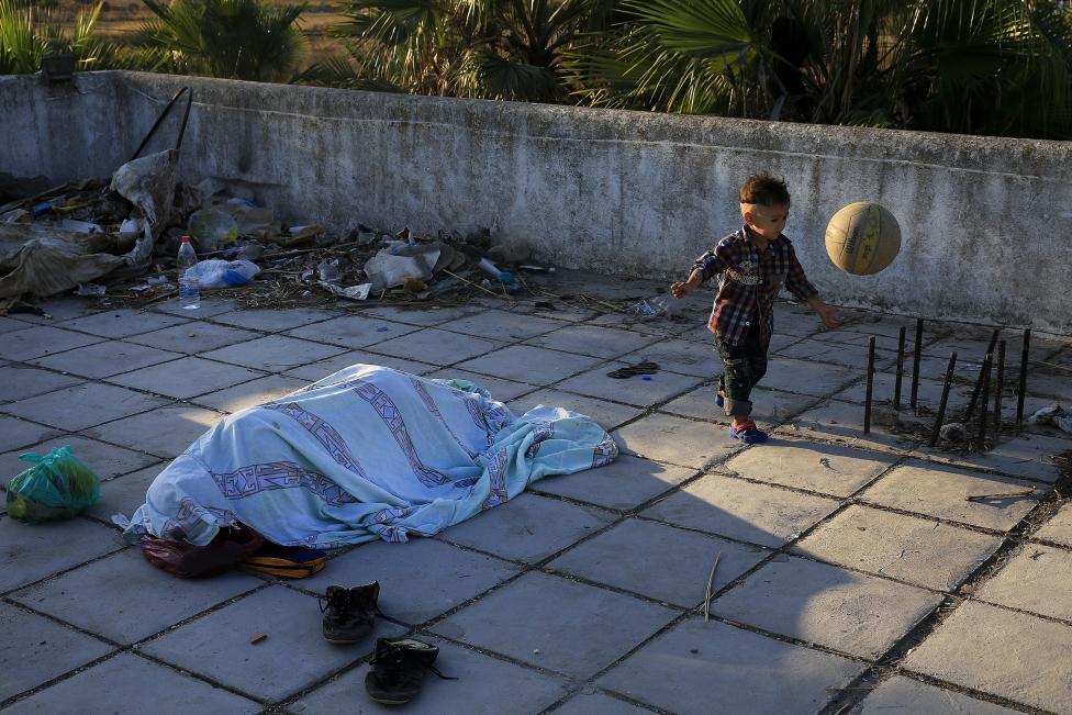 Bevándorló pakisztáni kisgyerek labdázik alvó apja mellett egy elhagyatott hotel tetején, a görög Kos szigeten. A megnövekedett migrációs hullám miatt a görög hatóságok egy stadionba zárták 24 órára a bevándorlók egy részét, többen pedig elhagyatott épületekben, hotelekben szállásolták el magukat. (f.: Reuters)