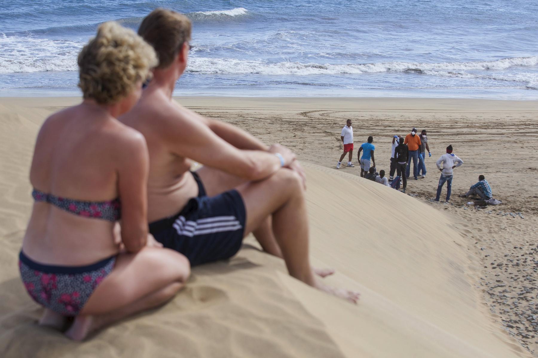Napozó turisták figyelik a partra érkező menekülteket a Kanári-szigeteken. (f.: AFP)