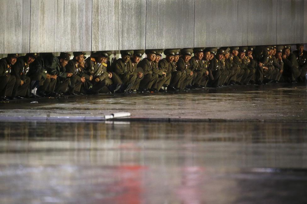 Tisztek próbálnak menedéket találni a rendezvényt elmosó vihar elöl. (f.: Reuters)