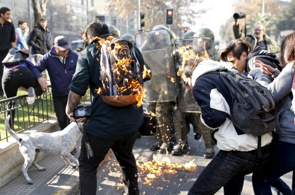 Tüntetők lángolnak, miután őket is elérte egy molotov-koktél által okozta robbanás. A chilei Santiago belvárosában hetek óta tüntetnek tanárok és diákok az oktatási rendszer reformjai érdekében. (f.: Reuters)
