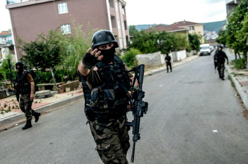 A török rendőrség különleges alakulatának egy tagja inti távolmaradásra a fotóst. Isztambulban két összecsapás is történt augusztus 10-én, hétfőn, amikor fegyveresek támadták meg a helyi amerikai nagykövetséget és egy rendőrkapitányságot is. (f.: AFP)