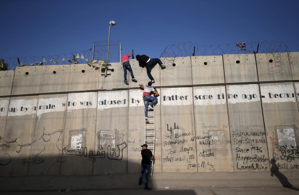 Palesztinok másznak át a Jeruzsálem és a Gázai-övezet között emelt falon, hogy részt vegyenek a ramadáni ünnepségeken és imákon. (f.: Reuters)