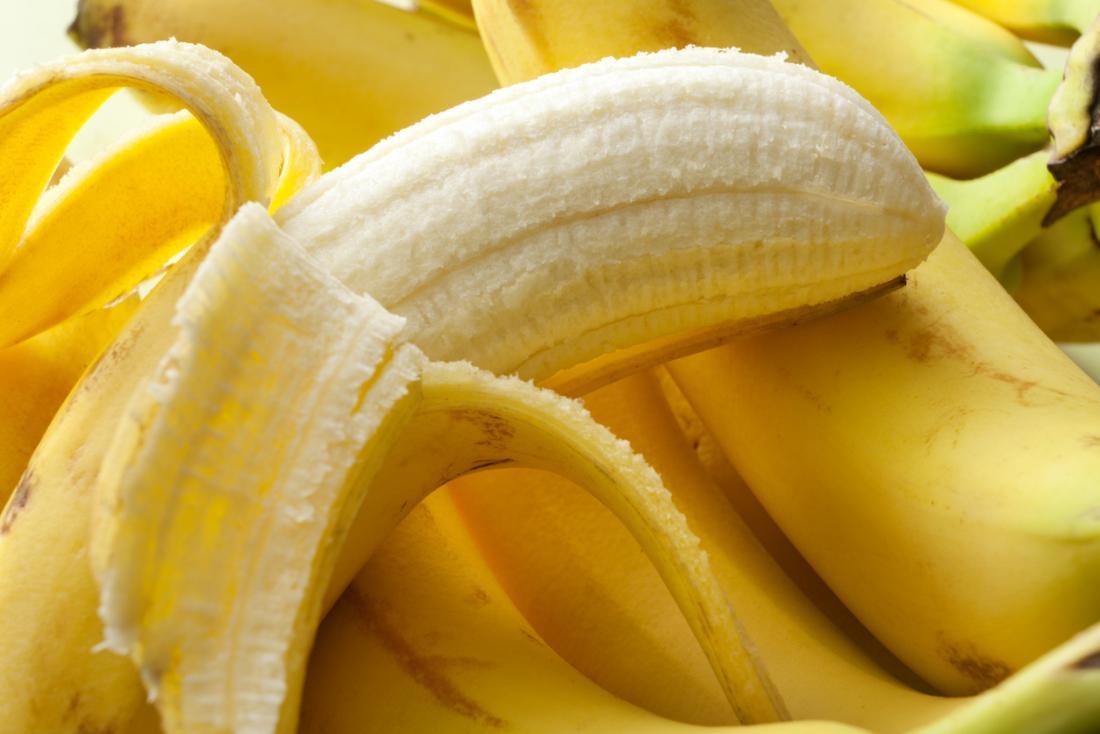 half-peeled-banana-on-top-of-bunch-of-bananas.jpg