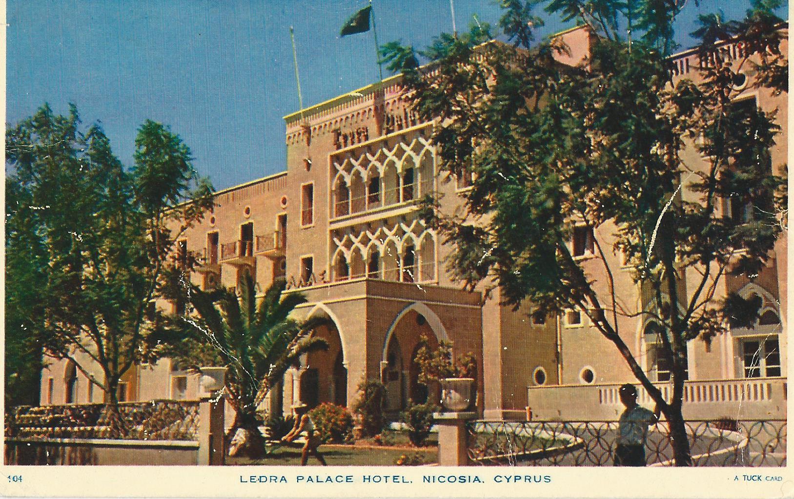 """A képeslapon a nicosiai Ledra Palace Hotel szálloda épülete látható, Ciprus fővárosában. <br />""""Drága Eszti néni és Bözsi néni! Sok-sok szeretettel csókolom mindkettőjüket ebből a paradicsomból. Itt olyan gyönyörű minden, nem tudunk hova nézni még mindig! Gyönyörű idő van, csupa pálma- és narancsfa az egész város, a tenger csodaszép! Ezt látni kell. Forró szeretettel csókolom mindnyájukat. Jutka"""""""