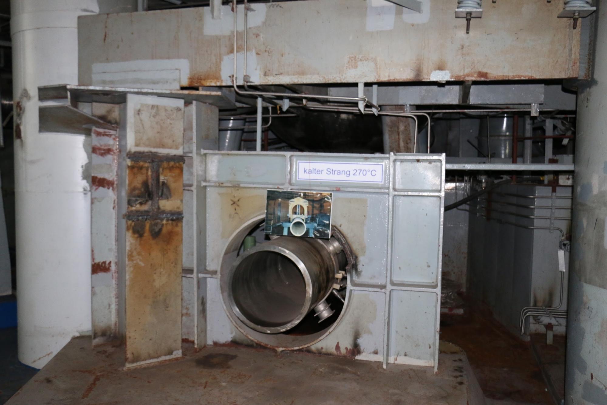 """A képen látható, nagy átmérőjű csöveken áramlik a hűtővíz be és ki a reaktortartályba. A balra alul lévő csonk a gőzfejlesztőből visszatérő, """"hidegági"""" csővezetékhez tartozott (itt a 270 Celsius-fokos visszatérő víz számít """"hidegnek""""). A másik csonk pedig a reaktort elhagyó, a gőzfejlesztő felé tartó, 315 fokos vizet szállító vezetéké. (A primer körben 123 bar nyomás alatt tartják a hűtővizet, ezért nem forr el – innen ered a nyomottvizes reaktorok neve.)"""