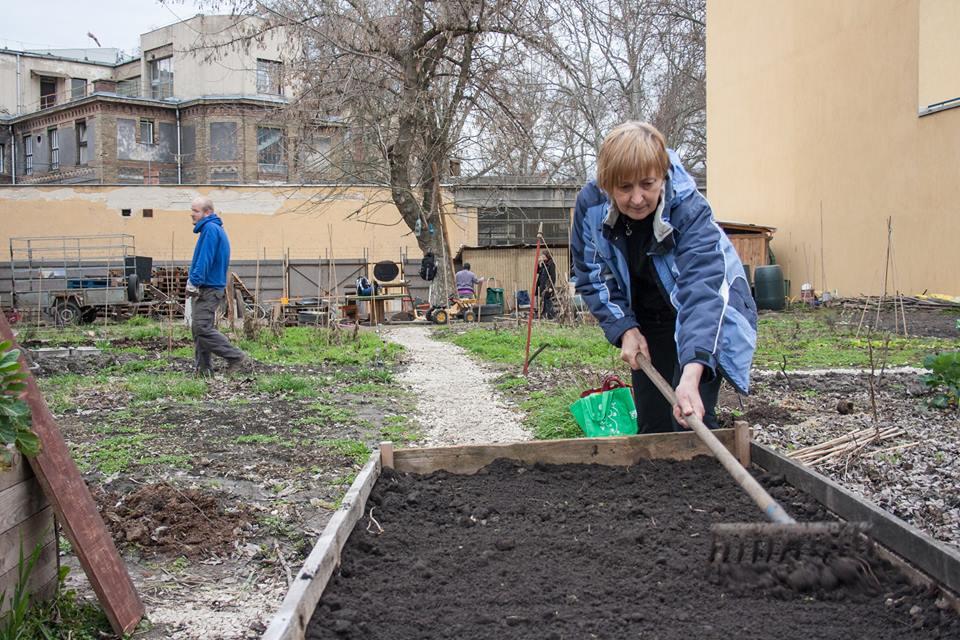 Rálátás a kertre - kék ruhás hölggyel, gereblyével és mosollyal.