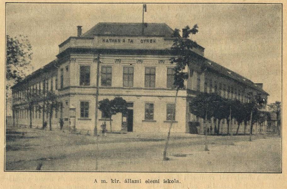 """Az 1. sz. nép-/elemi/általános iskola 1894-ben átadott épülete a Kossuth tér északnyugati sarkában. Érdekesség, hogy a """"Hatvan a tanügynek"""" felirat N és Ü betűje hiányzik, utóbbiból csak a két felső pont maradt. :)"""