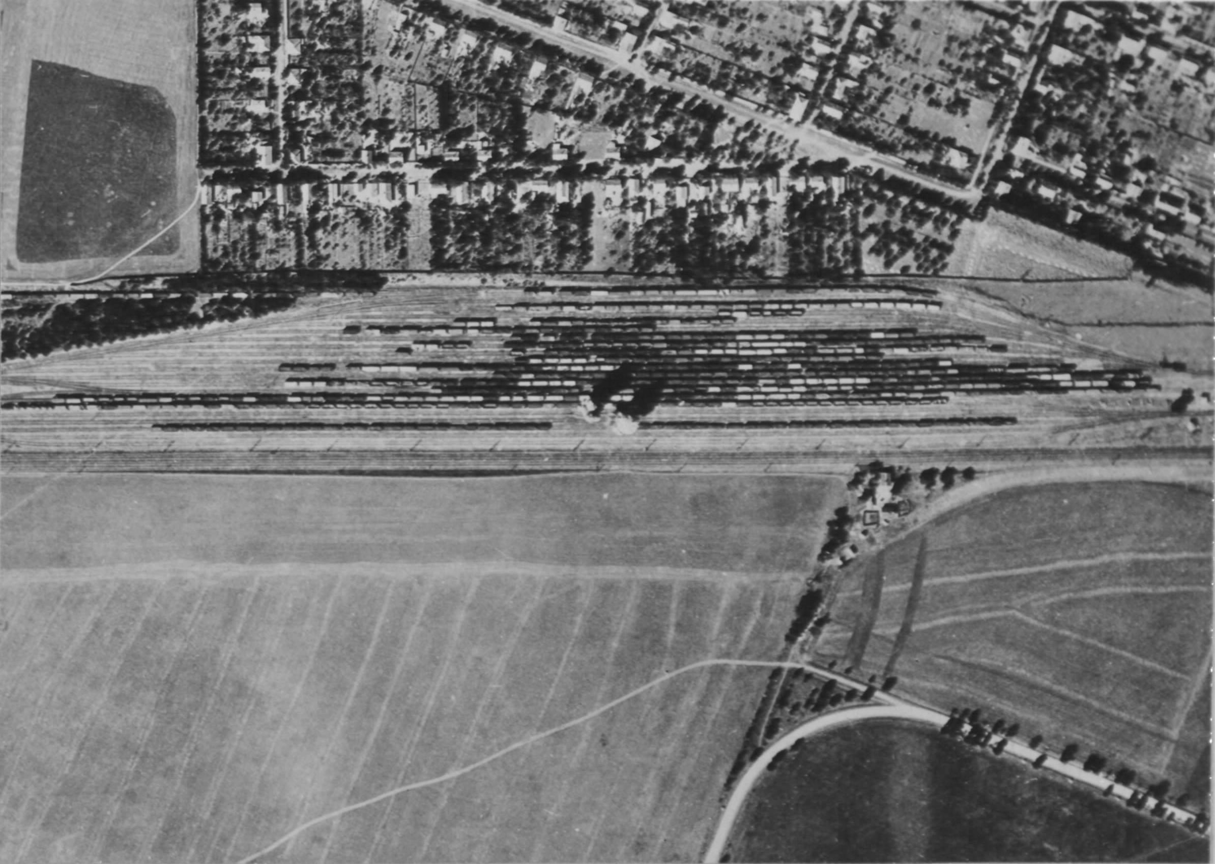 """A hatvani rendező pályaudvar, mint elsődleges célpont, a támadás pillanatában. A vágányokon várakozó német hadiszállítmány-szerelvények. Jól kivehető a Teleki/Thököly/Lehet utca háromszöge; a kép baloldalán lévő """"üres"""" területen épült fel 30 évvel később az újhatvani strand. (USA NA / USAAF szabad hozzáférésű archívuma)"""