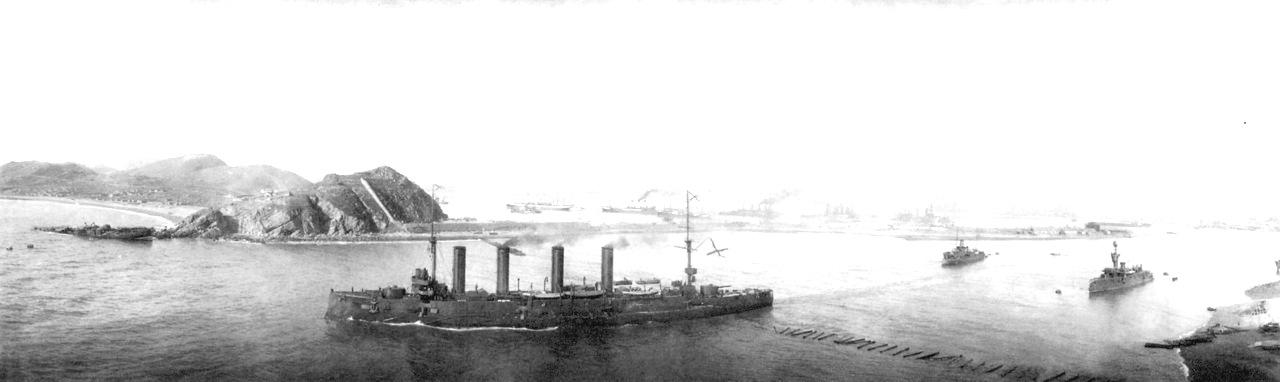 A távol-keleti orosz flotta legjobb cirkálója, a Bajan, kifut Port Arthurból. Jobbra lent jól látható a kikötő bejáratát védő gát.