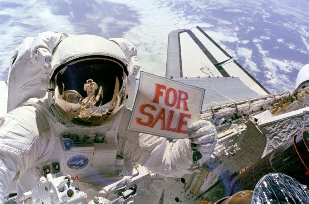 """Űrhajós egy űrsétán, kezében egy """"Eladó"""" felirattal"""
