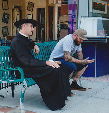 822643p13628ednmain21872father_carney_talking_to_man_with_tattoos_1.jpg