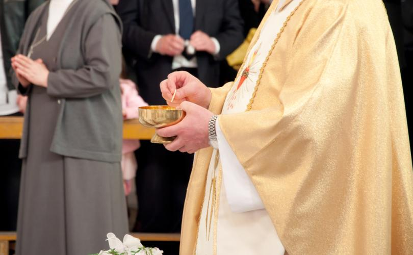 catholic_priest_giving_communion_810_500_75_s_c1.jpg