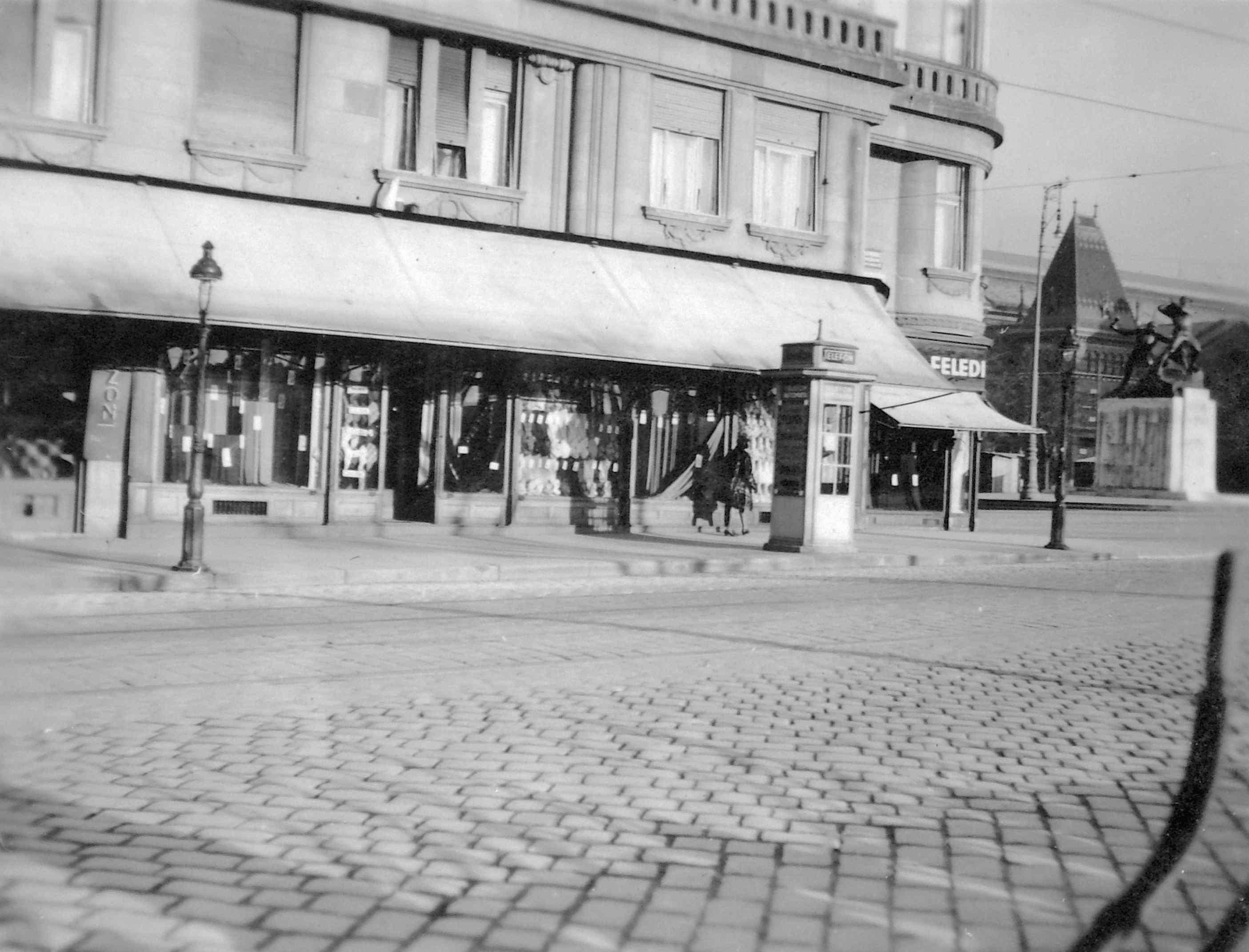 A ház földszintjén a rakpart felőli oldalon is üzletek működtek.<br />A Belgrád (Ferenc József) rakpart - Fővám tér sarka 1935 körül, háttérben az 1. honvéd és népfölkelő gyalogezred emlékműve a Fővám téren.<br />Forrás: Fortepan #07582