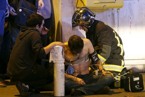 french-fire-brigade-members-aid-an-injured-individual-near-the-bataclan-concert-hall.jpg