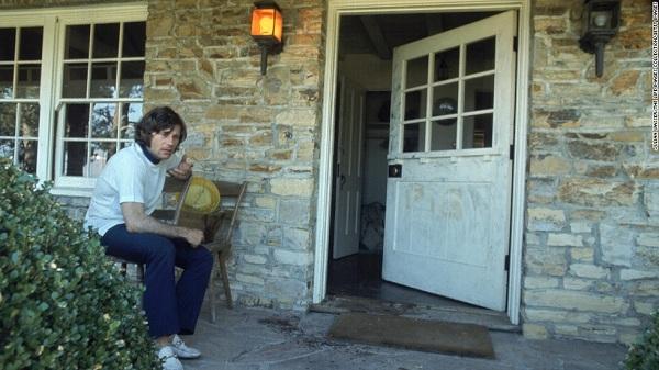 Polanski nem volt otthon a gyilkosságok idején - a képen a háza előtt ül, az ajtón még látszik a PIG (disznó) felirat