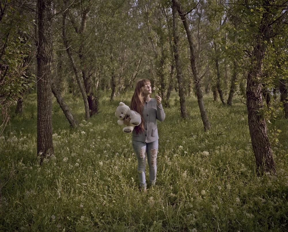 Fotó: Bácsi Róbert László: Anna Anit 17 éves lány a Dnyeszter partján születésnapjára kapott mackóval. 2015. Részlet a Transznisztria sorozatból
