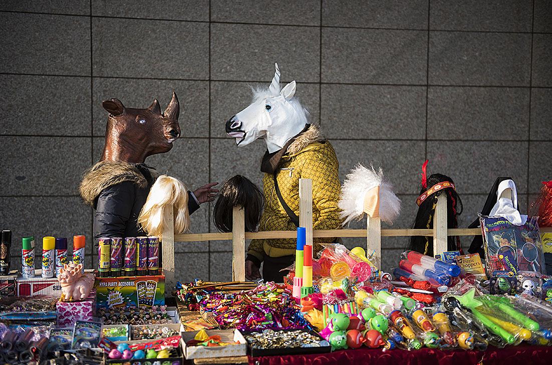 Fotó: Balázs Attila: Szilveszteri maszkokat árusító asszonyok beszélgetnek Nyíregyházán, egy bevásárlóközpont előtt, 2016<br />
