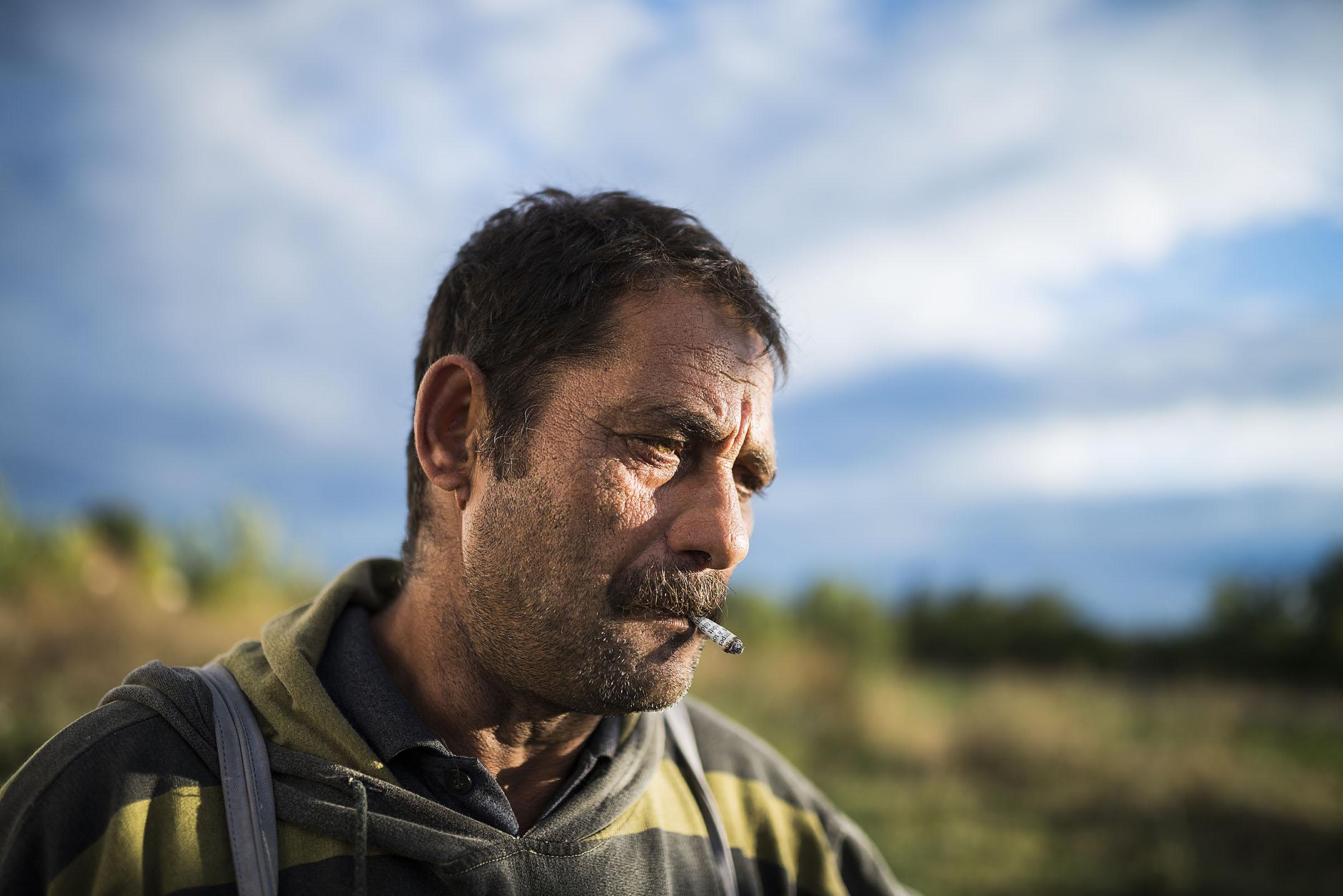Fotó: Balázs Attila: Egy férfi újságpapírba tekert dohányt szív Józsefházán. Az elszegényedett falusi lakosság körében gyakori, hogy cigarettahüvelyre sem telik. Részlet a Dohány című sorozatból, 2013