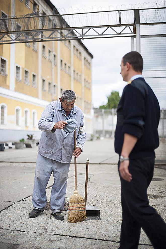 Fotó: Balázs Attila: Rontó Tihamér elítélt sapkáját levéve üdvözli a börtön egyik tisztjét a Sátoraljaújhelyi Fegyház és Börtön udvarán. Az elítéltek minden esetben így köszöntik a börtön dolgozóit, 2011<br />