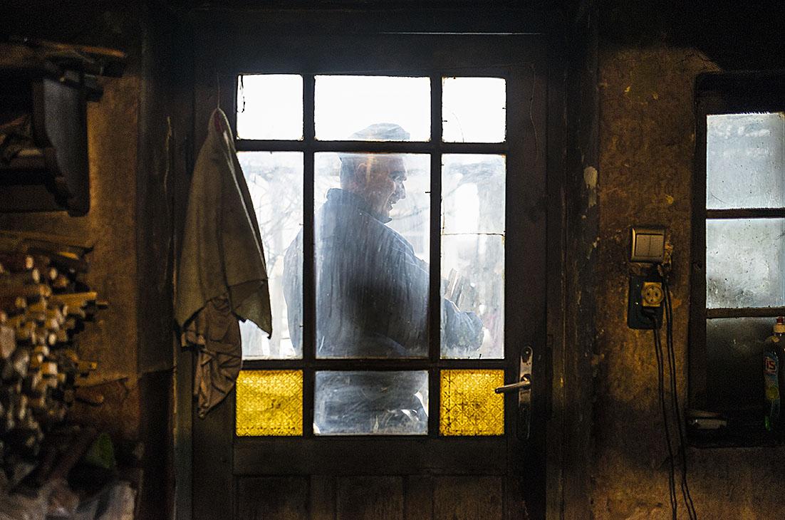 Fotó: Balázs Attila: Turóczi László címzetes rendőr főtörzszászlós egy ölnyi fát visz egy segítségre szoruló idős ember házába Rókabokorban, 2016<br />