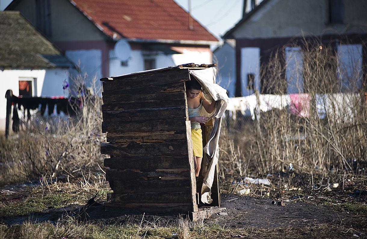 Fotó: Balázs Attila: Egy fiatal lány kilép az udvari WC függönye mögül Tiszavasváriban. Részlet a Legyen cigány Magyarországon című sorozatból, 2011<br />