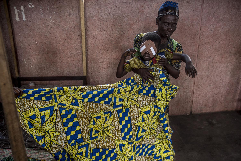 Fotó: Hajdú D. András: Az altatásból ébredező Mbedjit a nagymamája viszi haza az ablaktalan sárkunyhóba, amit szívességből kaptak kölcsön egy távoli rokontól néhány napra.