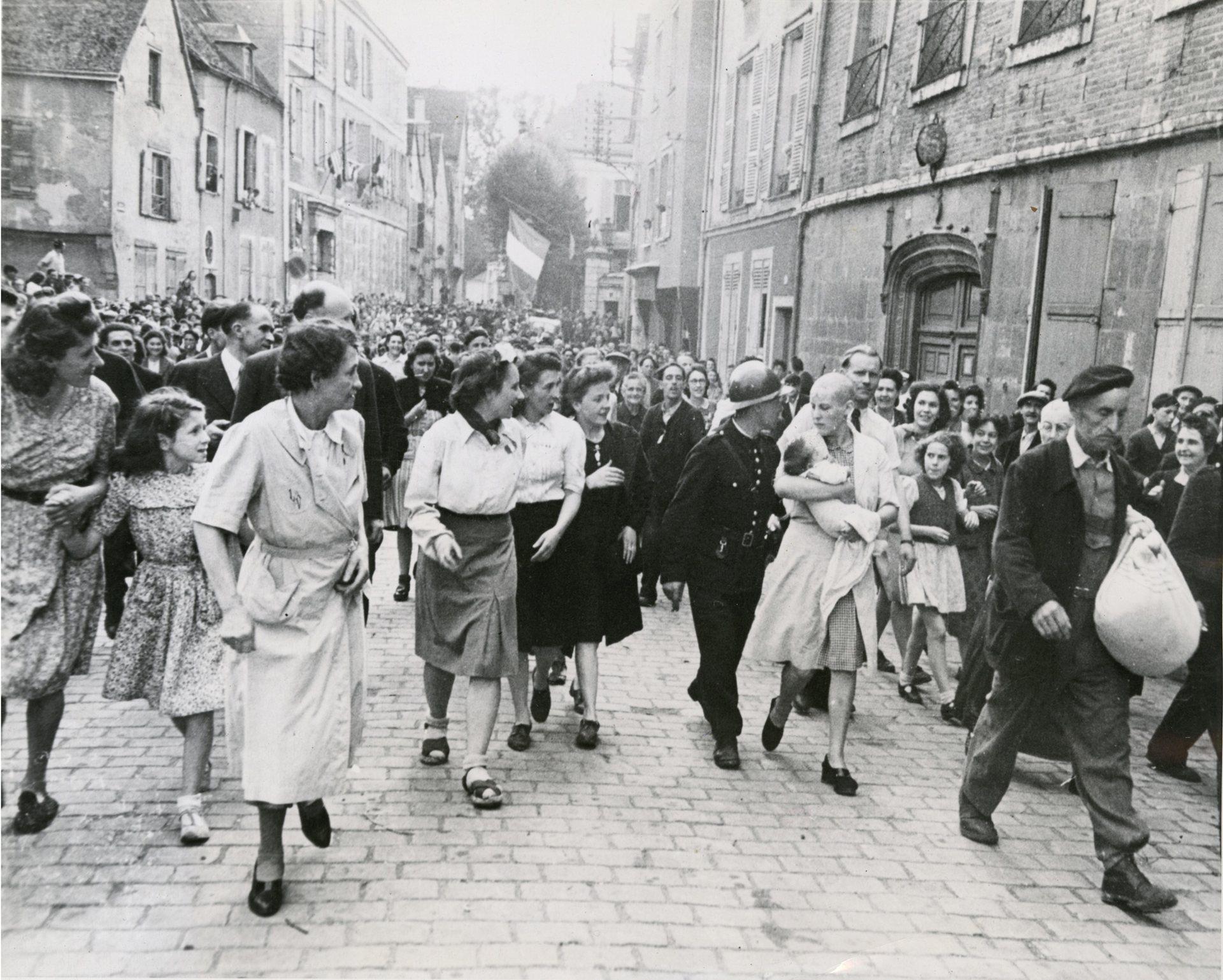 """Fotó: Robert Capa: Borotvált fejű francia nő, akinek gyereke született egy német katonától.<br />Chartres, Eure-et-Loir, 1944. augusztus 18. © Robert Capa / Magnum Photos <br /><br />Robert Capa 1944. augusztus 18-án a franciaországi Chartres városában készítette el világhírű fotóját, amelyet maga élete legjobb felvételének tartott.<br />""""Döbbenetes volt a német katonától származó gyereket magához szorító nő és körülötte az eltorzult, gyűlölködő arcok. Hát ezt szeretem, mert sikerült emberi mélységeket megmutatni rajta."""" (In: Markos György: Barátom, Capa)"""