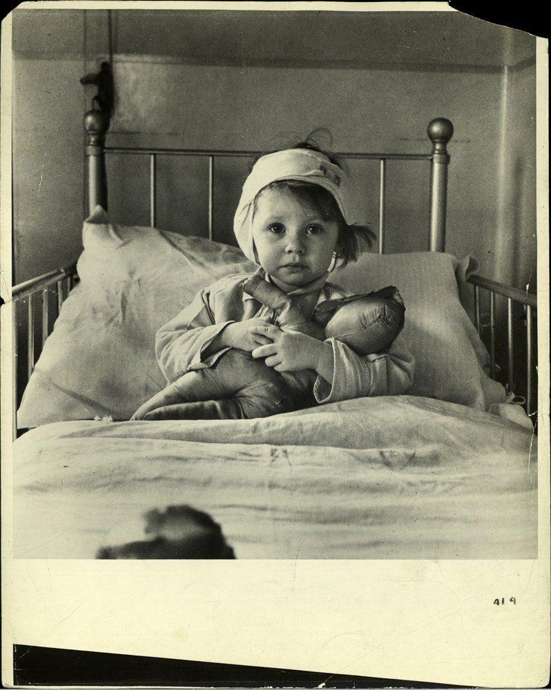 """Fotó: Cecil Beaton: Eileen Dunne, Great Ormond Street Hospital, London, 1940 © Cecil Beaton/ Camera Press/ Redux<br /><br />A Brit Hírszerzési Minisztérium megbízásából készült ikonikus fotón egy sebesült kislányt láthatunk, aki bekötött fejjel szorongatja maciját egy nagy kórházi ágyon. A fotó egyik változata először a The Illustrated London News képeslap címlapján jelent meg 1940. szeptember 21-én az alábbi szöveggel: """"A bombázás következményei: Göring London elleni támadásának gyerekáldozatai."""""""