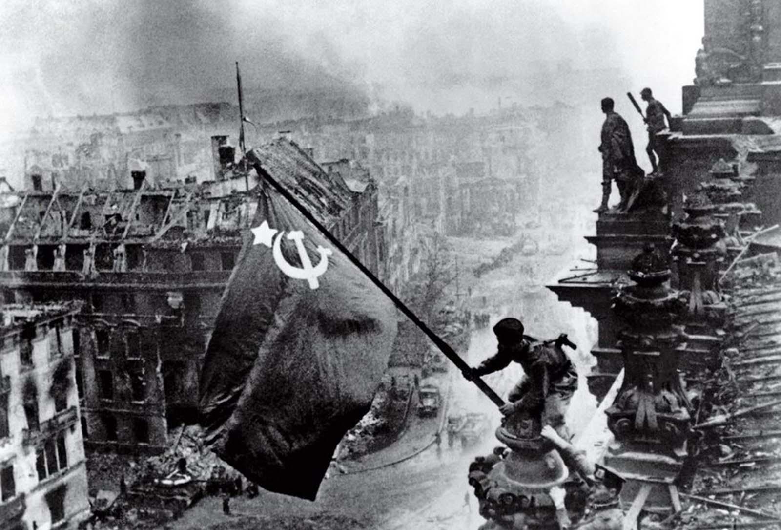Fotó: Jevgenyij Haldej: Raising the Banner of Victory, Berlin, 1945. május 2. © Jevgenyij Haldej:<br /><br />A Jevgenyij Haldej zászlót kitűző katonájának fotóját - mely már a Mai Manó Házban is bemutattuk - számtalan legenda övezi, és az is biztos, hogy egy újrajátszott pillanatát láthatjuk történelmünknek.