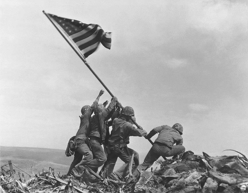 Fotó: Joe Rosenthal: Raising the Flag on Iwo Jima, 1945. február 23. AP Photo<br /><br />Itt is a történelem egy újrajátszott pillanatát látjuk. A délelötti zászlóállítás után Rosenthalnak sikerült az Easy Company hat tengerészgyalogosát rávennie az általa elképzelt feladatra. Ők állították fel a nagyobbra cserélt zászlót 12.30-kor, egy Rosenthal által megkomponált és beállított jelenet közben, s később ez a fotó járta be a világot, s vált a leghíresebb és legtöbbet reprodukált fotók egyikévé.