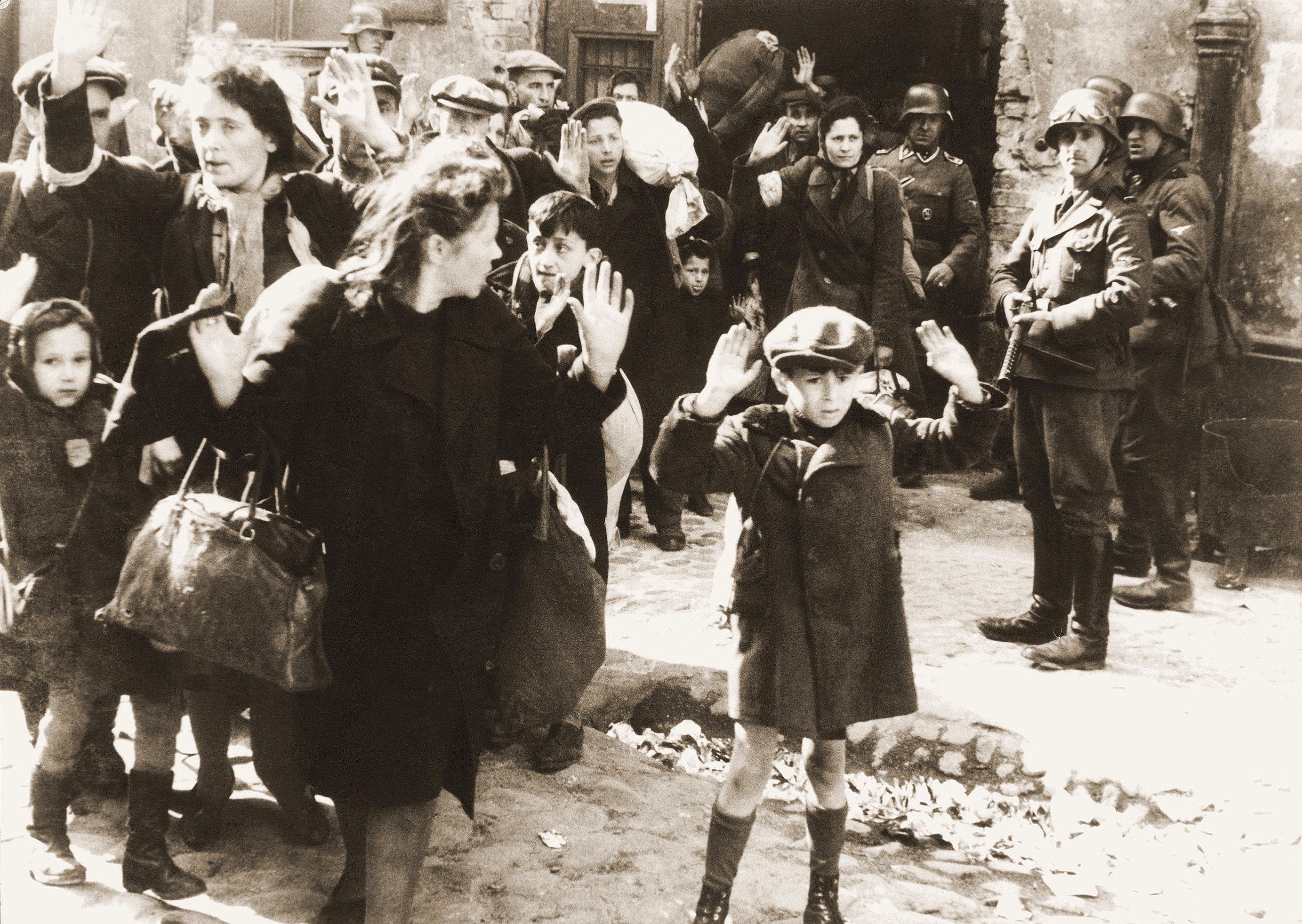 """A náci holokauszt egyik legbeszédesebb fotóját 1943 áprilisában készítette a varsói gettófelkelés leverésekor egy SS-katona.<br /><br />A támadást vezető Stroop """"Varsóban nincs többé zsidónegyed"""" címmel 75 oldalas jelentést állított össze a gettó felszámolásáról, melyet 52 fotóval illusztrált. Ezek egyike a felemelt kezű kisfiút ábrázoló kép is. Hogy a fotó pontosan kit ábrázol, arról megoszlanak a vélemények. Az igazság a fiú nevéről talán már soha nem derül ki, de a holokauszt egyik németek által dokumentált, leghíresebb fotójának drámai hatása és üzenete örökké megmarad."""
