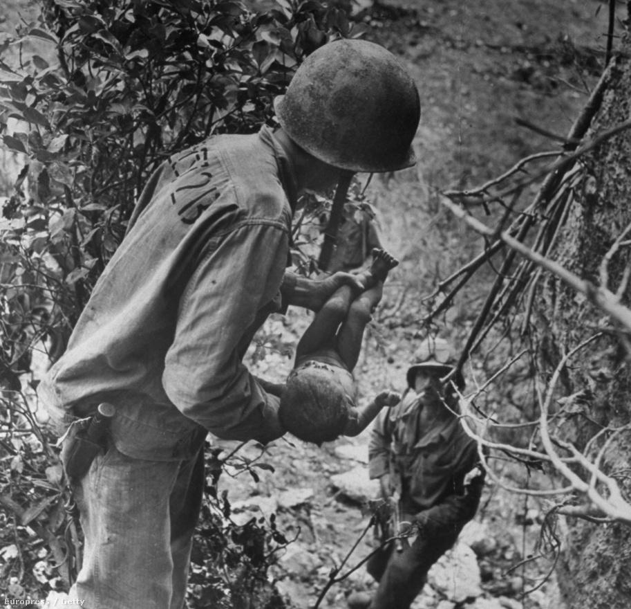 Fotó: W. Eugene Smith: Japán, 1944<br /><br />A fotográfust a világháborús felvételei tették igazán ismertté. Ezen a képen egy amerikai tengerészgyalogos egy súlyosan sérült csecsemőt ringat a második világháború japán frontján. A kis testet arccal lefelé találták egy barlangban, ahova a japánok az amerikai támadások elől húzódtak be.