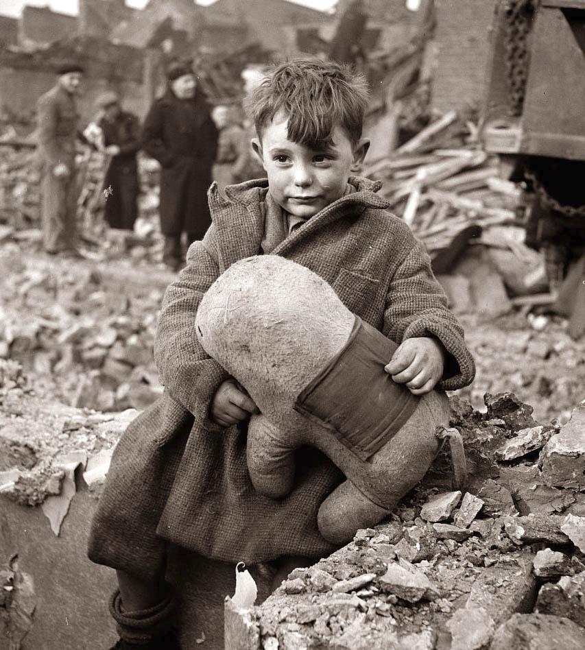 Fotó: Toni Frissell: Elárvult kisfiú ül otthona romjain, London, 1945 <br /><br />Toni Frissell 1945-ben, Londonban készítette világhírű fotóját, melyen a romokon üldögélő kisfiú kitömött állatfiguráját szorongatja. A kisfiú éppen játszani volt barátaival mikor a bombázást jelző szirénák megszólaltak, mire hazaért már csak a lerombolt otthonát találta meg, szülei és testvére a romok alatt lelték halálukat.