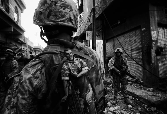 Fotó: Anja Niedringhaus: A US Marine of the 1st Division carries a GI Joe mascot as a good luck charm in his backpack while his unit pushes further into the western part of the city,<br />Fallujah, Iraq, November 2004<br />© picture alliance / AP Images