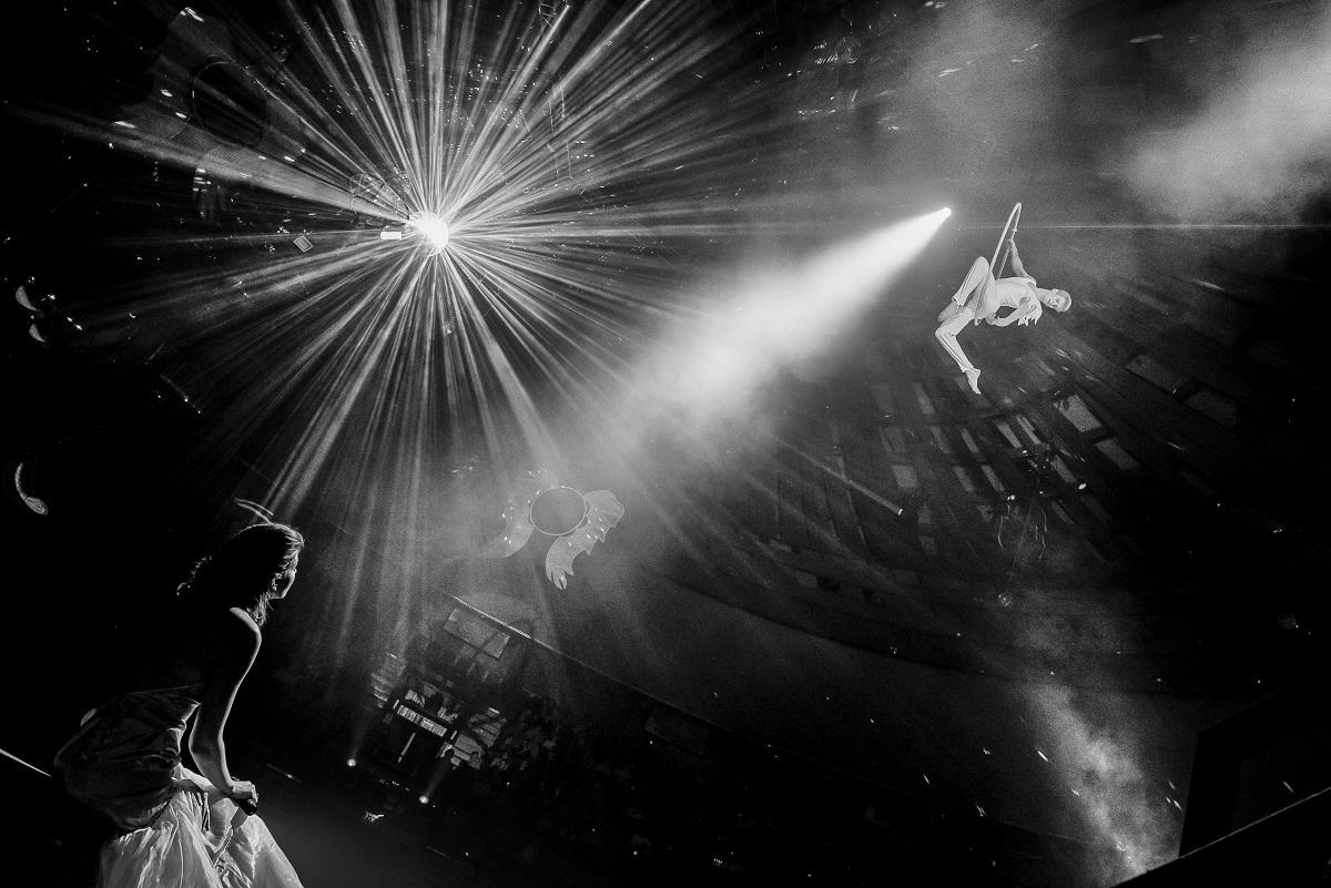 Művészet 3. díj<br /><br />Fotó: Zsolnai Péter: Fent és lent<br /><br />A cirkusz mindig a csillogásról és az együttműködésről szól. A mai virtuális világ  határtalan pörgés élményéhez képest lassúnak tűnik a bemutató. Amikor az ember belép a nézőtérre és beleszippant a manézs illatába, megpillantja az artisták műsorát és el kezd tódulni az adrenalin.
