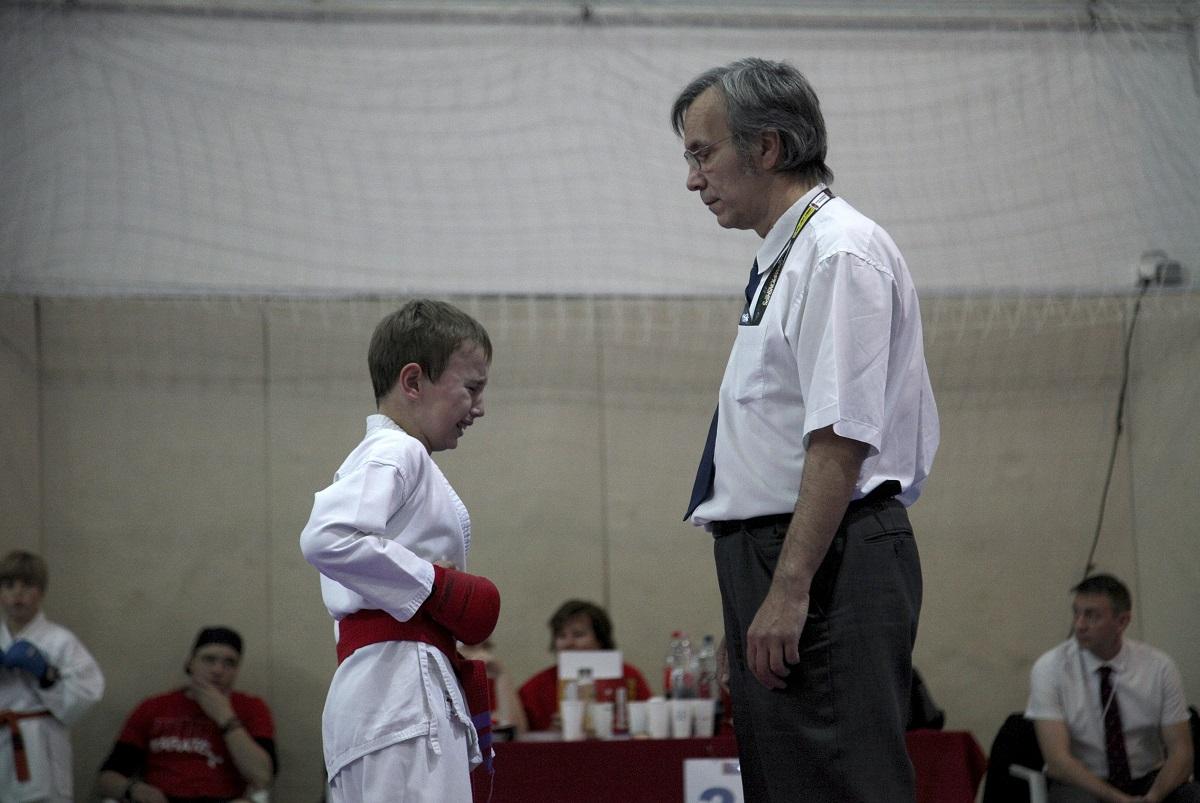 Sport 1. díj<br /><br />Fotó: Balázs Imola: Fájdalom<br /><br />A 23. Budapesten rendezett Kodomo Kupán a képen látható fiúra nagy rúgást  mért ellenfele. Gyorsan kellett döntenie, folytatja e a versenyt, vagy feladja. Pár másodperc elteltével legyőzte fájdalmát és tovább folytatta a küzdelmet.