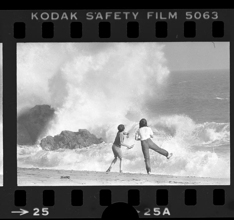 Fotó: Két fiatal nézi, ahogy a hullámok megtörnek a sziklákon, Point Mugu State Park, Calif., 1979 © UCLA Library/Los Angeles Times