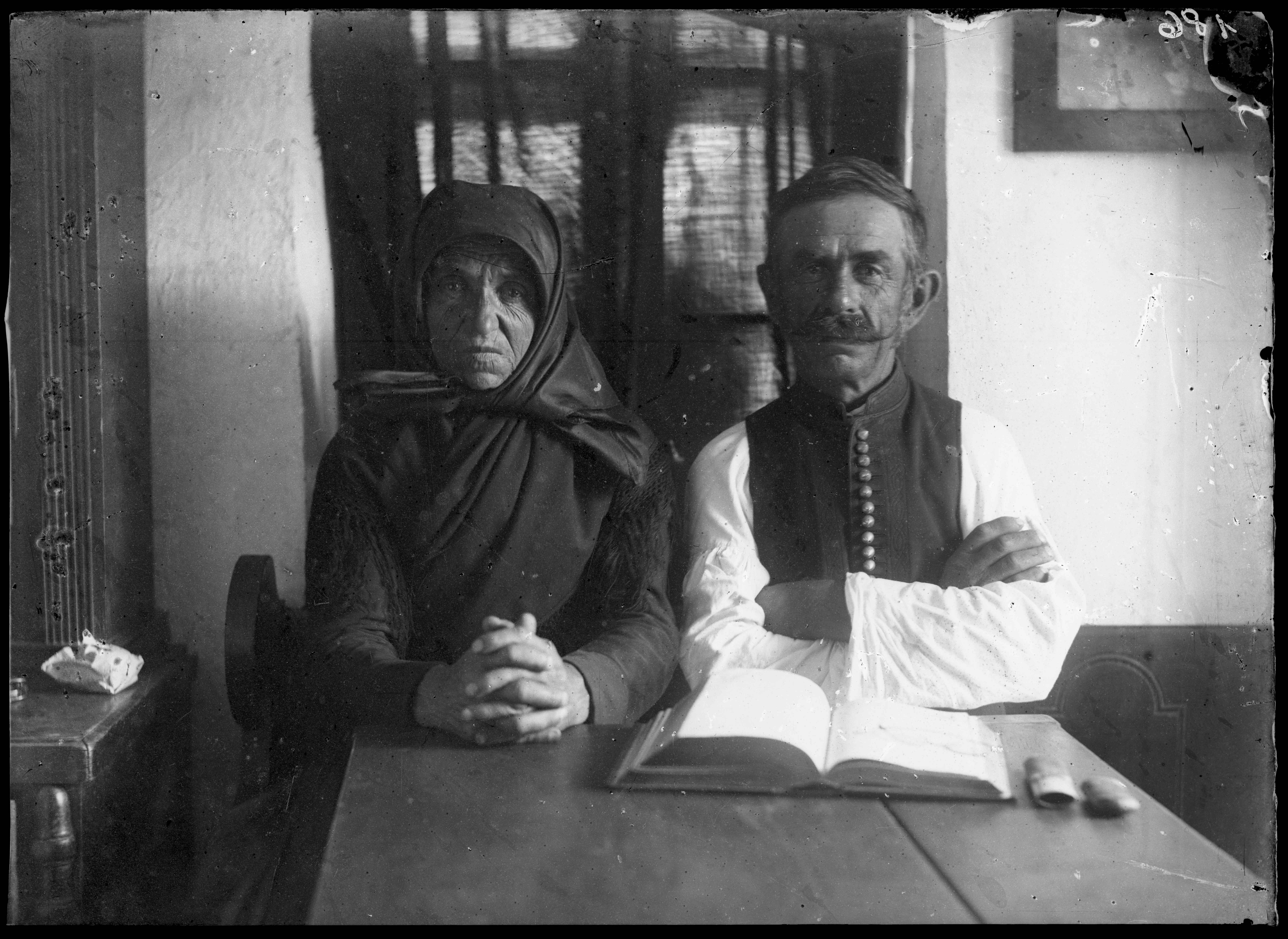 Fotó: Plohn József: Tornyai János édesanyja és egy idős férfi asztal mögött ül, előttük Biblia. © Tornyai János Múzeum gyűjteménye, Hódmezővásárhely