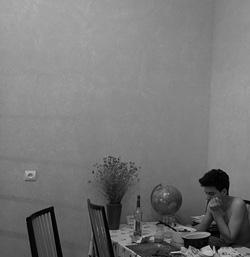 [A félmeztelen szerző földgömbje mellett ételeket néz az ebédlőasztalnál]