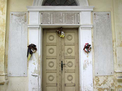 Az elesettek neveit tartalmazó fehér márvány emléktáblák a kápolna kapuja körül