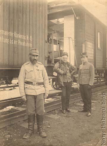 A cs. és kir. 45. sz. állandó kórházvonaton szolgáló egyik idős népfelkelő és a háttérben a kórházvonat tisztjei (balról jobbra): Parányi ezredorvos, vonatparancsnok, mellette Kósa György